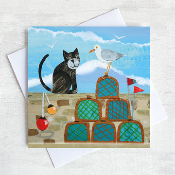 A coastal greetings card featuring a black cat in conversation with a cheeky seagull. They are on a harbour wall surrounded by lobster pots.
