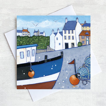 A greetings card featuring a painting of Crail on the Fife coastline. There is a fishing boat in the foreground that is surrounded by creels and lobster pots.