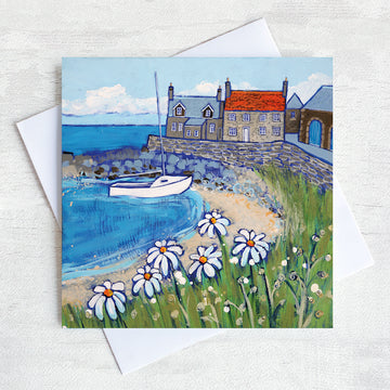 A greetings card featuring a colourful painting of craster harbour with daises in the foreground and a sailing boat in the bay.