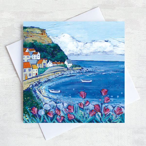 A greetings card featuring a painting of Brunswick bay with pink flowers in the foreground and a blue sky above the quaint village on the cliff side.