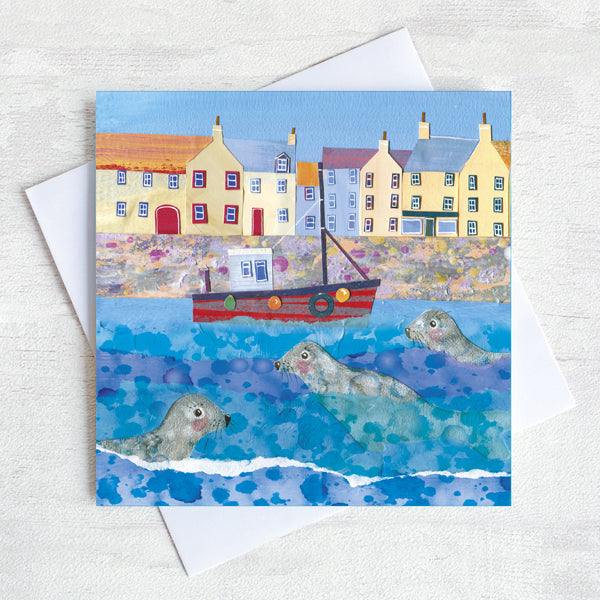 A greetings card of coastal harbour featuring seals bobbing in the water around a fishing boat.