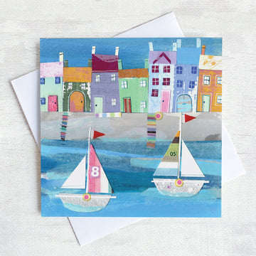A greetings card featuring a paper collage of a cute harbour with colourful cottages and sailing boats on the water.