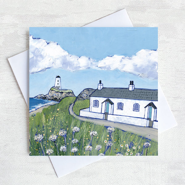 A greetings card featuring the white cottages and lighthouse on llanddwyn island on Anglesey with clover  flowers peppered in the foreground.