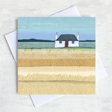 A greetings card featuring a traditional scottish blockhouse with a black roof and a red door. In front is a field of grass.