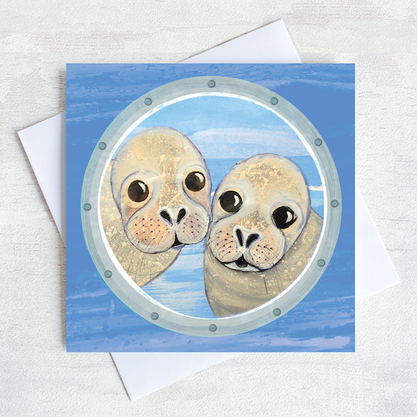 A greetings card featuring two cheeky seals peeking through a ships porthole.