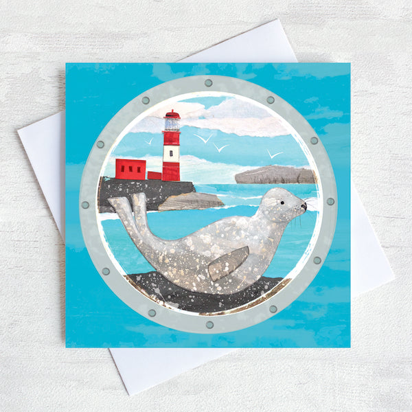A greetings card featuring a grey seal basking on the rocks in front of a red and white lighthouse.