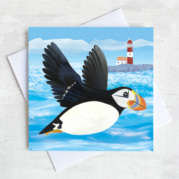 A coastal greetings card with a flying puffin swooping over a quirky red and white lighthouse.