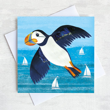 A coastal greetings card featuring a flying puffin over a turquoise sea.