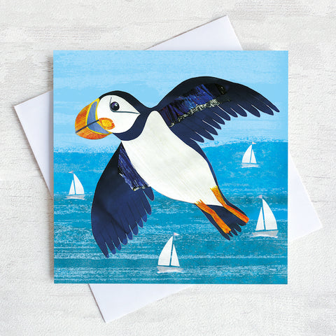 A greetings card featuring a flying puffin over a turquoise sea.