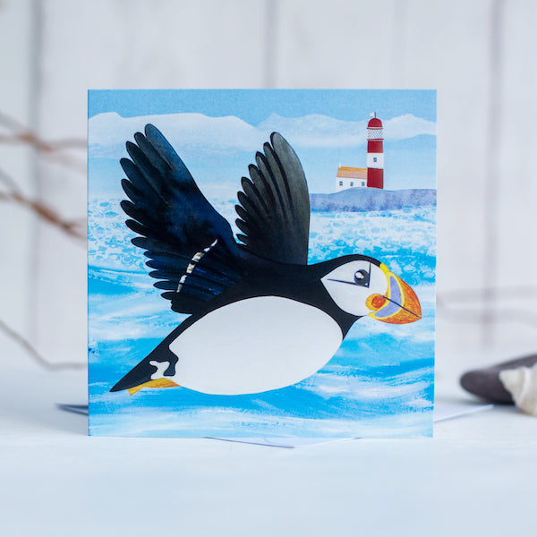 A greetings card featuring a flying puffin in front of a quirky little lighthouse.