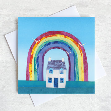 A Greetings Card featuring a white cottage with a colourful rainbow  overhead.
