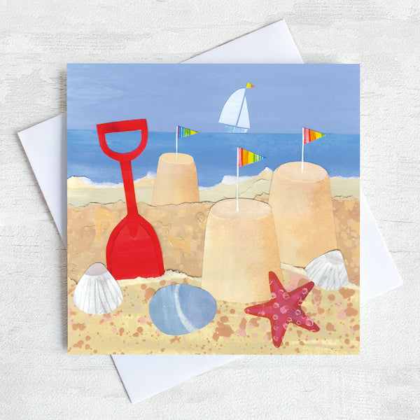 A greetings card featuring a seaside scene of sandcastles, buckets and spades.