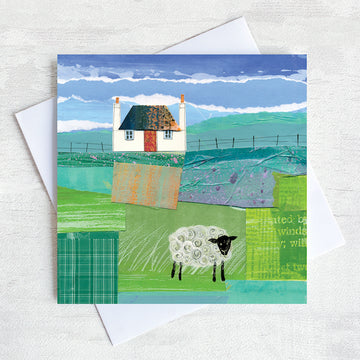 A scottish greetings card featuring a collaged artwork of a traditional blockhouse with a red door and a black headed sheep grazing in the field in front of the house.