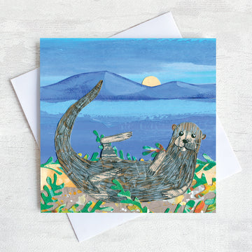 A greetings card with a sea otter curled on a moonlit beach surrounded by seaweed.