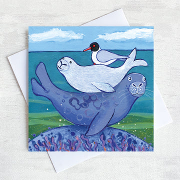 A charming greetings card from an original painting by Joanne Wishart, this joyous picture features a seal pub on its mum back with a friendly seagull snuggled on top!