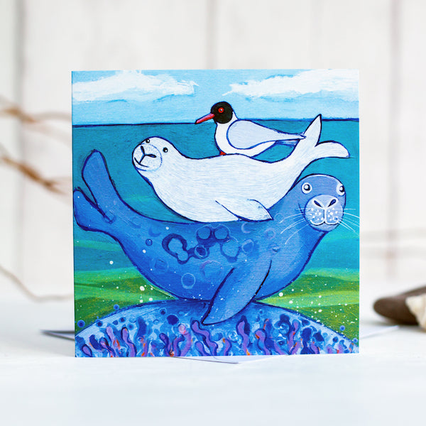 A greetings card featuring a cute family of seals snuggled on each others back, with a black headed gull on top.