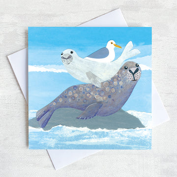 A cutsy seaside greetings card featuring a seal with it's pup on its back with a friendly seagull.