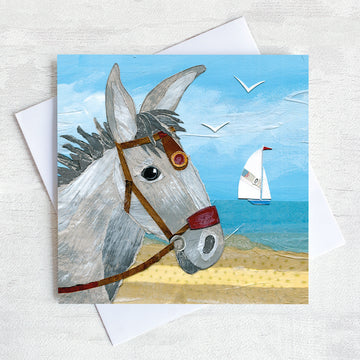 A coastal greetings card featuring the portrait head of a seaside donkey standing on a beach with a sailing boat in the distance on the sea.