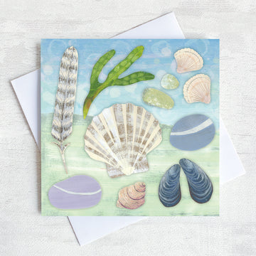 A greetings card featuring everything you may find on a beach collection. Pebbles, shells, feathers and seaweed.