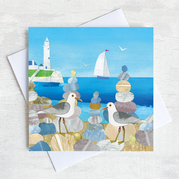 Greetings card featuring two seagulls on a beach with st mary's lighthouse in the background.