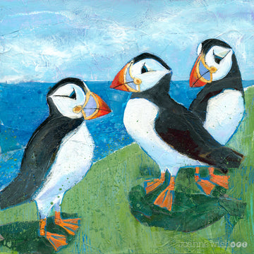 An art print of 3 cheeky puffins perched on a grassy ledge above the bright blue sea.