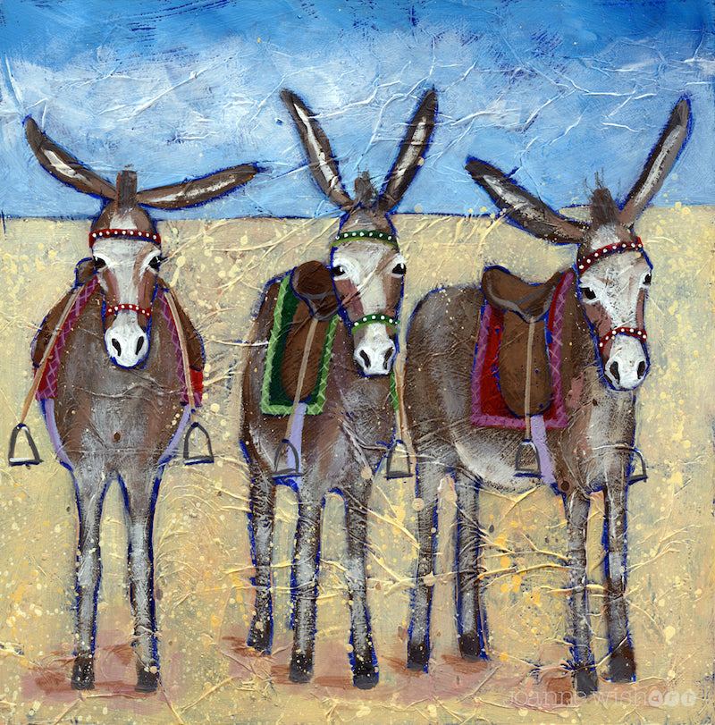 A print of three cute donkeys lined up in row on the beach.
