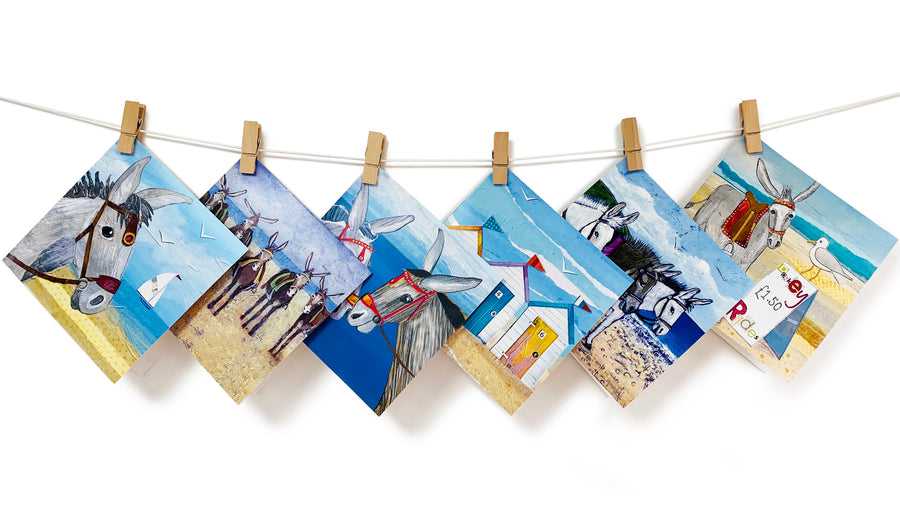 A selection of colourful greetings cards inspired by the seaside. Including Donkeys and beach huts.