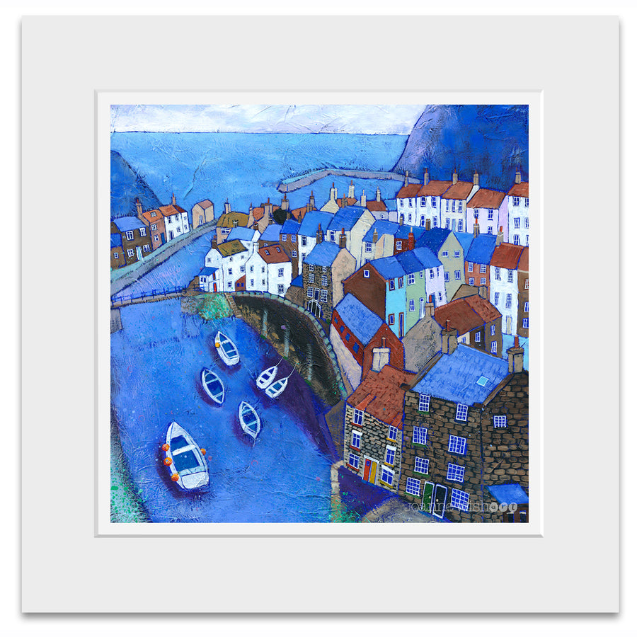 A mounted print of Staithes village.