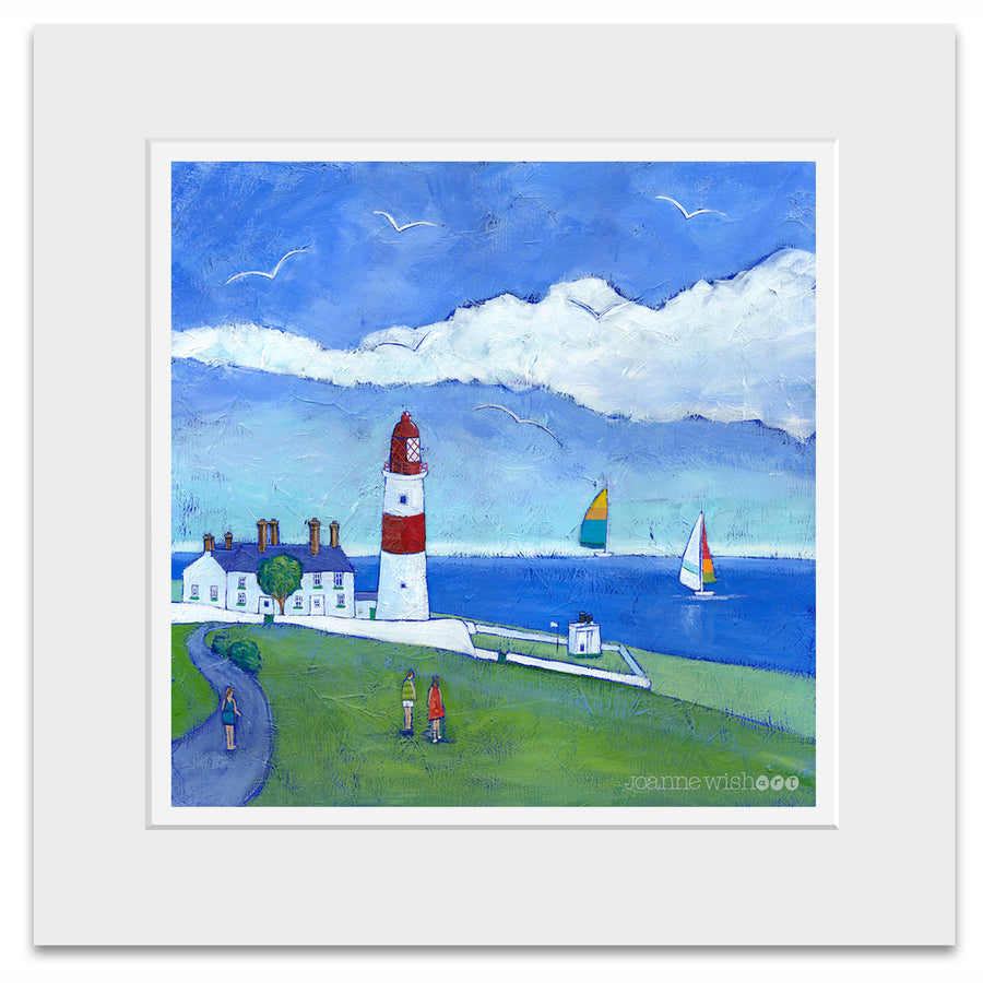 A mounted print of Souter lighthouse featuring sailing boats out at sea and people walking by.