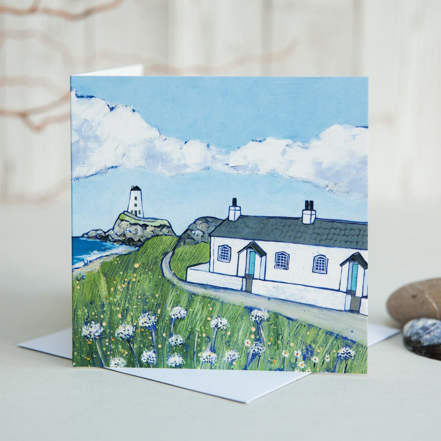A greetings card featuring a painting of the white cottages and lighthouse on Llanddwyn Island off Anglesey.