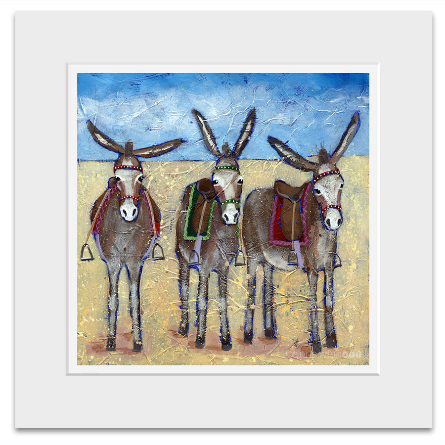 A mounted print of three cute donkeys lined up in row on the beach.