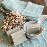 Mint herbal bath bars displayed in a bowl with beautiful dried flowers.