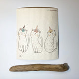 Natural cloth with 3 white cats  outlined in black with pastel unicorn style hats.