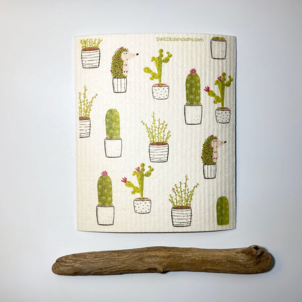 Natural cloth displaying a cactus collage in green, white, with black outlines.