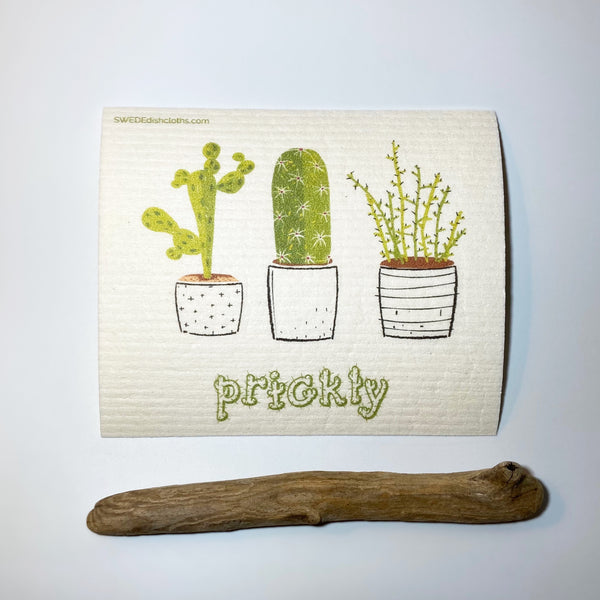 Cloth with three whimsy cactus plants displayed with rustic birch wood.
