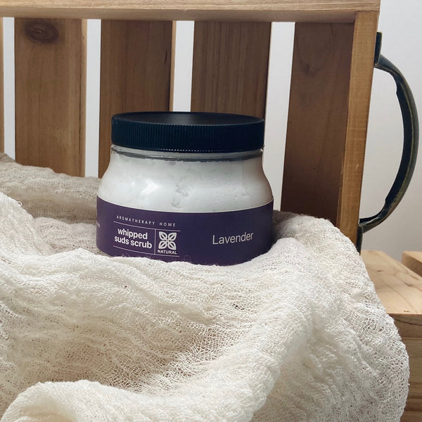 Lavender whipped suds scrub displayed with a wooden box and cheese cloth.