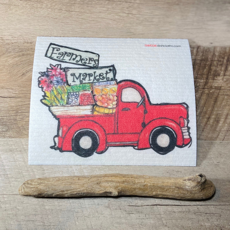 Farmers red truck filled with vegetables and flowers