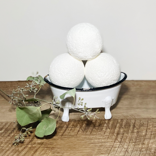 Eucalyptus Peppermint bath bombs in a vintage tub prop with eucalyptus sprig.