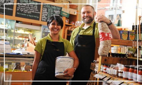Nik and Sangita holding artisan deli items in front of the deli counter