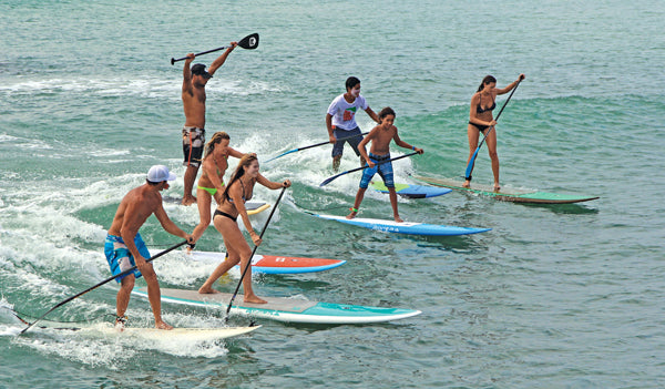 Image of multiple SUP paddlers sharing a wave all on Riviera boards.