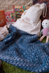 Hand-crocheted, large blanket in denim blue.