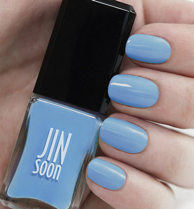 Hand holding light blue nail polish Aero by JinSoon