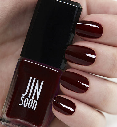 Hand holding deep red nail polish Audacity by JinSoon