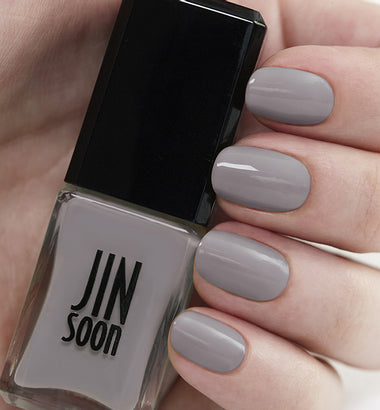 Hand holding grey nail polish bottle by JinSoon