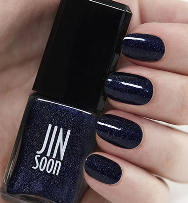 Hand holding dark sparkly blue nail polish bottle by JinSoon