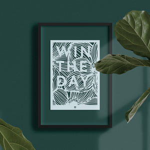 Win the Day laser cut wall art in light blue card on dark wall