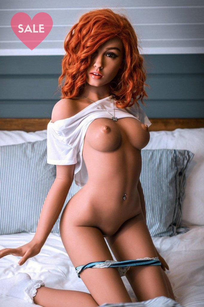 Charlotte, a realistic sex doll by WM-Dolls with Red hair, half naked & kneeling on a bed.