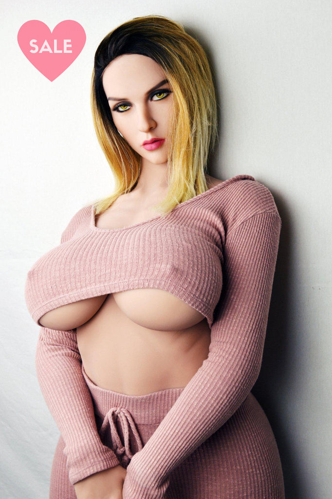 Suzy, a realistic sex doll by WM-Dolls with big boobs, blonde hair and pink clothes.