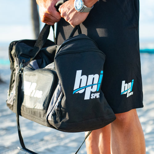 Man holding the BPI Sports duffle bag at the beach