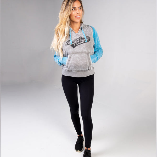 Woman wearing the Ladies BPI Sports Training Pullover Hoodie with blue sleeves and grey front